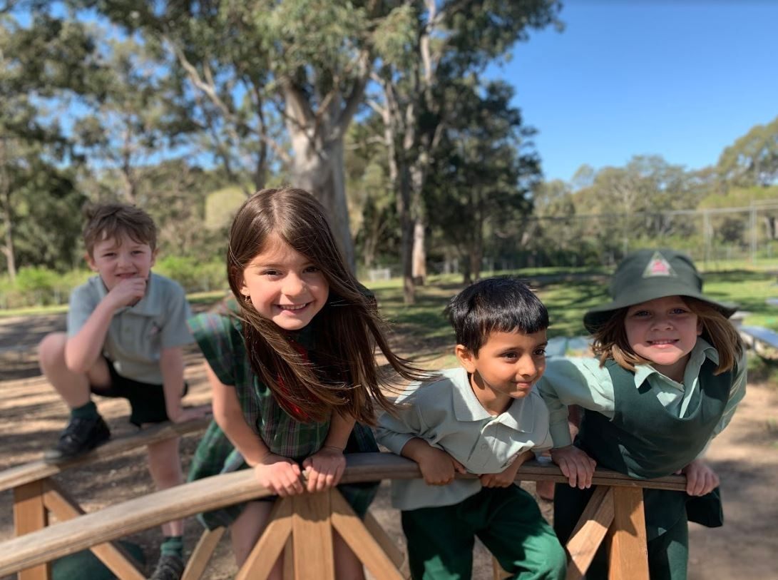 Four kindergarten students playing outside in the playground